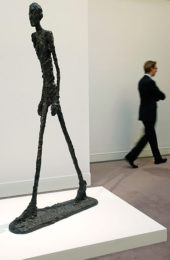 A man walks next to L'homme qui Marche I, by Alberto Giacometti